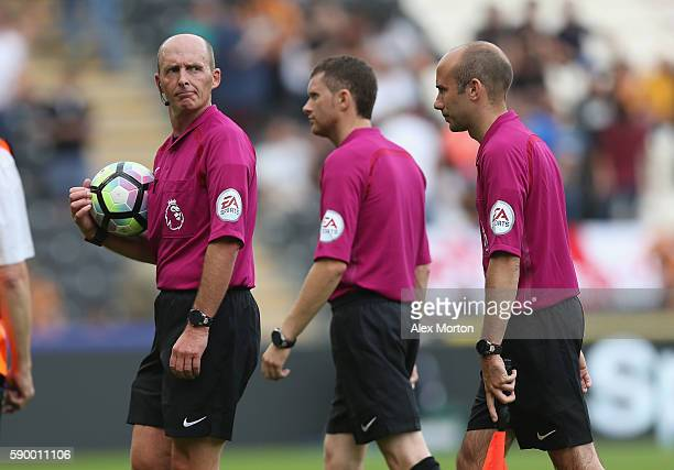 Match referee Mike Dean and assistants walk off at half time during the Premier League match between Hull City and Leicester City at KC Stadium on...