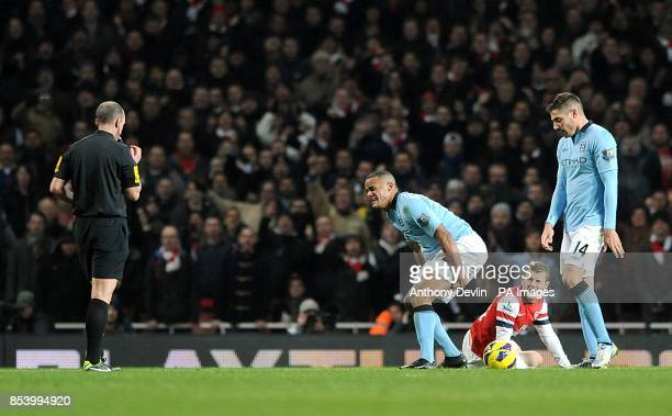 Match referee Mike Dean prepares to send off Manchester City's Vincent Kompany after a foul on Arsenal's Jack Wilshere