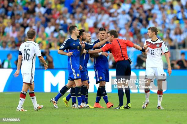Match referee Nicola Rizzoli holds back Germany's Thomas Muller as Argentina players confront him during the FIFA World Cup Final at the Estadio do...