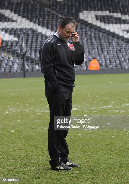 Match referee Rob Styles talks on his mobile phone before calling off the match at Craven Cottage
