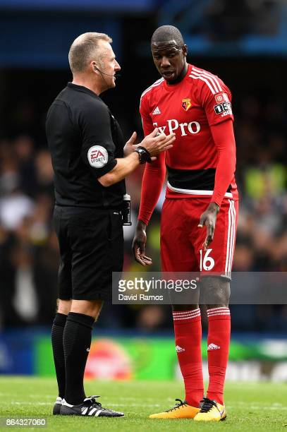 Match referee speak with Abdoulaye Doucoure of Watford during the Premier League match between Chelsea and Watford at Stamford Bridge on October 21...