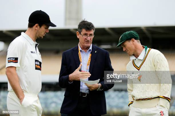 Match referee Steve Bernard talks to team captains Mitchell Marsh of the Warriors and George Bailey of the Tigers about the rain delay during day one...