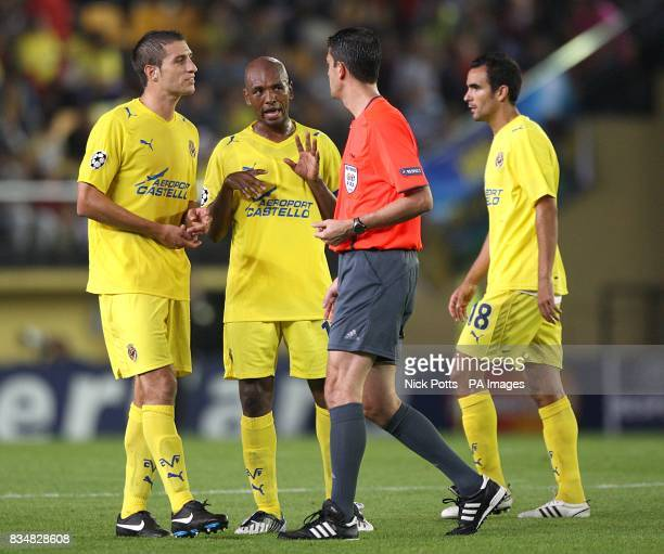 Match referee Viktor Kassai is confronted by Villarreal's Lopez Angel Robert Pires and Marcos Senna on the stroke of half time