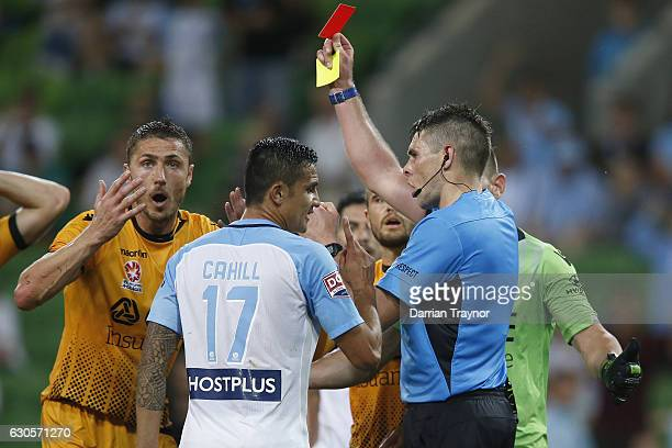 Match refereee gives a red card to Rostyn Griffiths as team mate Joseph Mills of Perth Glory argues during the round 12 ALeague match between...