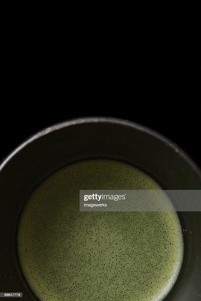 Matcha (Japanese powdered green tea)  against black background, close-up : Stock Photo