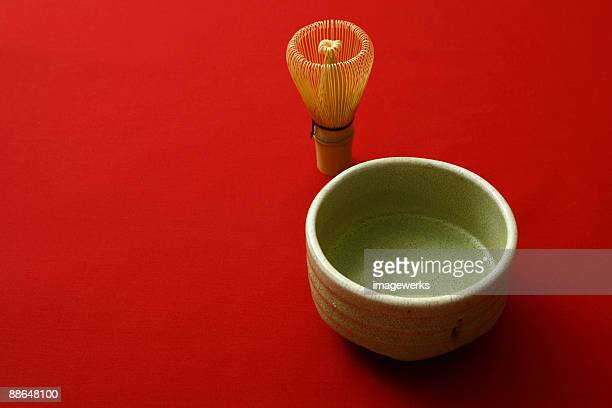 Matcha (Japanese powdered green tea) and tea whisk against red background, close-up