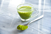 Culinary powdered matcha and matcha latte on a marbled table