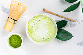 Matcha green tea latte in a cup and tea ceremony utensils. Copy space