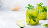 Matcha iced green tea with lime and fresh mint on a marble background. Copy space.