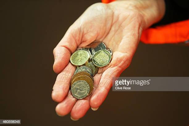 A matchday steward holds a handful of coins that were thrown in the direction of Theo Walcott of Arsenal during the Budweiser FA Cup third round...