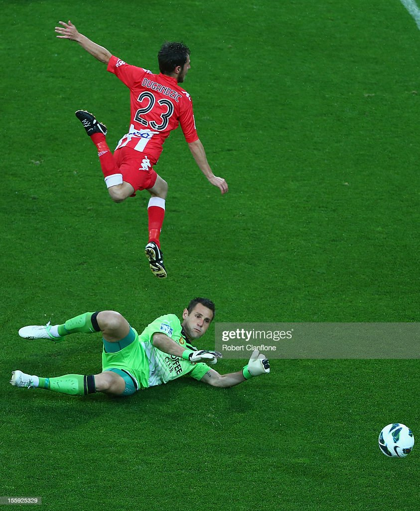 Mate Dugandzic of the Heart is challenged by Roar goalkeeper Michael Theo during the round six A-League match between the Melbourne Heart and the Brisbane Roar at AAMI Park on November 9, 2012 in Melbourne, Australia.