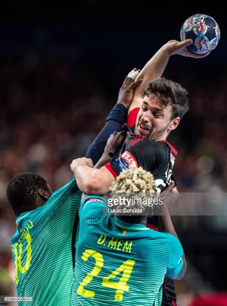 Mate Lekai of Veszprem is attacked by Cedric Sorhaindo and Dika Mem of Barcelona during the VELUX EHF FINAL4 3rd place match between Telekom Veszprem...