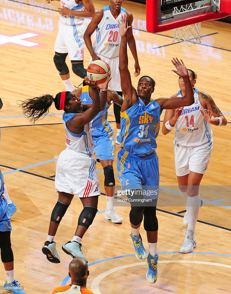 Matee Ajavon of the Atlanta Dream puts up a shot against Sylvia Fowles of the Chicago Sky on July 13 2014 at McCamish Pavilion in Atlanta Georgia...