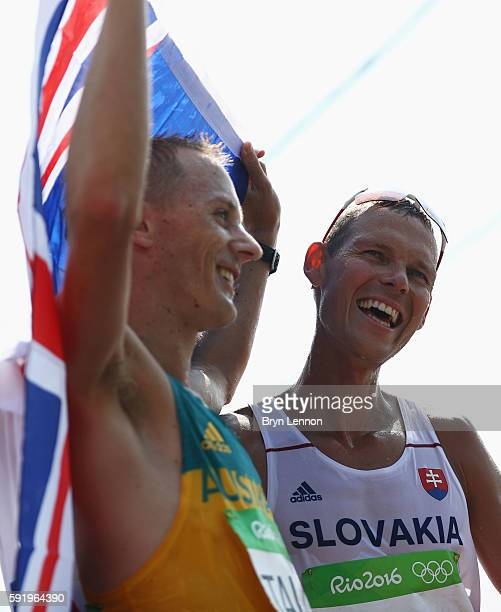 Matej Toth of Slovakia celebrates winning the gold medal alongside silver medalist Jared Tallent of Australia in the Men's 50km Race Walk on Day 14...
