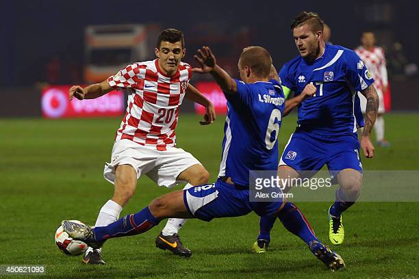 Mateo Kovacic of Croatia is challenged by Ragnar Sigurdsson and Aron Gunnarsson of Iceland during the FIFA 2014 World Cup Qualifier playoff second...