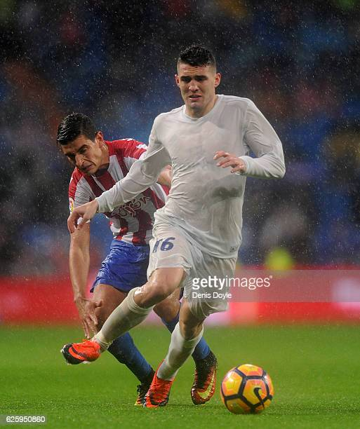 Mateo Kovacic of Real Madrid runs past Rachid AitAtmane of Real Sporting de Gijon during the La Liga match between Real Madrid CF and Real Sporting...