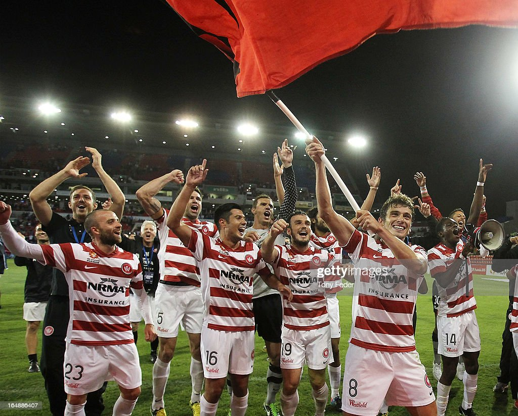 Mateo Poljak of Western Sydney waves a flag in front of team mates after victory over the Jets in the round 27 A-League match between the Newcastle Jets and Western Sydney at Hunter Stadium on March 29, 2013 in Newcastle, Australia.