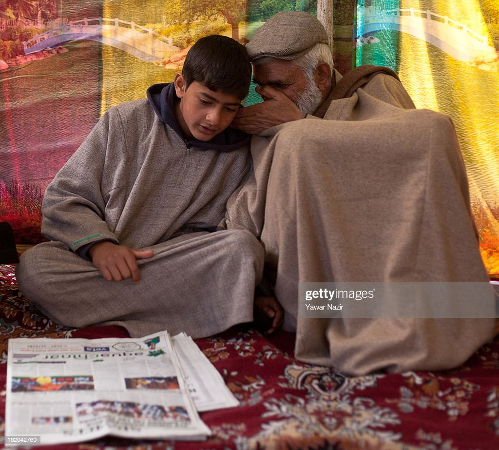 Maternal grandfather wishers in the ear of 14-year-old Ghalib Afzal Guru, the son of executed Kashmiri separatist Afzal Guru, as he reads a newspaper at his residence on February 18, 2013 in Jagir, Sopore, 50 km (31 miles) north of Srinagar, the summer capital of Indian-administered Kashmir, India. Guru was secretly hanged and buried at the Tihar Jail in India's capital, New Delhi, on February 9 for his alleged role in the 2001 attack on the country's Parliament. His family alleges that they were kept in dark about the execution by the Indian government . Apprehensive of a massive public fallout over the execution, Indian authorities clamped a curfew for seven consecutive days in Kashmir even as three people were killed allegedly in Indian government forces' action during protests and clashes . Meanwhile, separatist groups have called for a three day strike beginning Wednesday to press the Indian government for handing over of Guru's mortal remains to his family for his last rites, a demand growing louder by the day in Kashmir.