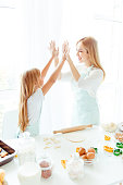 Maternity parenthood white light win winner tasty finished complete concept. Vertical side view photo of cheerful excited cute lovely sweet charming mommy small kid giving high-five in light kitchen