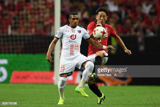 Mateus of Omiya Ardija and Tomoya Ugajin of Urawa Red Diamonds compete for the ball during the JLeague J1 match between Urawa Red Diamonds and Omiya...