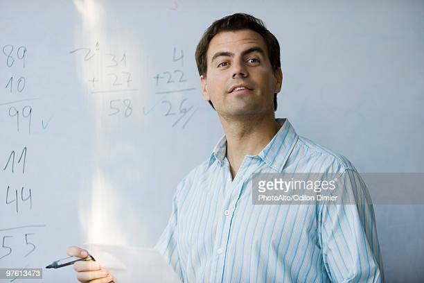 Math teacher in front of whiteboard, looking expectantly