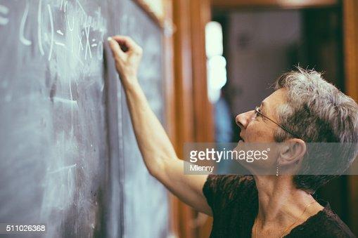 Mathemathics professor at chalkboard writing formula
