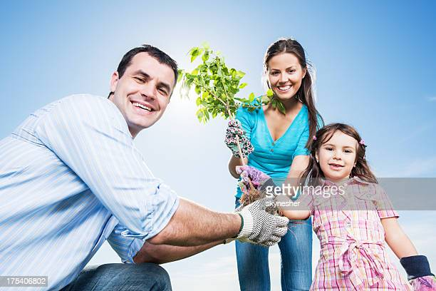 Mather, father and their daughter gardening on beautiful day.
