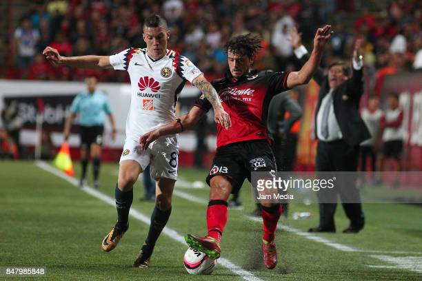 Mateus Uribe of America and Matias Aguirregaray of Tijuana fight for the ball during the 9th round match between Tijuana and America as part of the...
