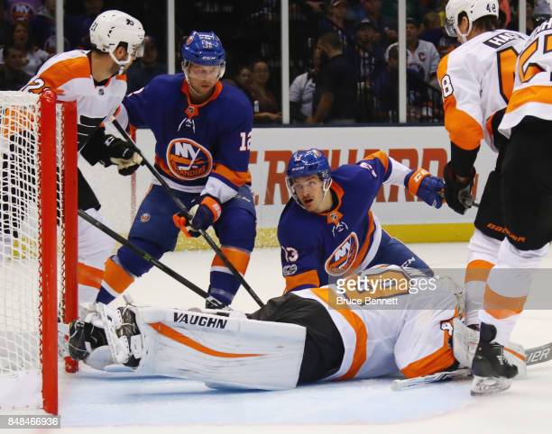 Mathew Barzal and Josh Bailey of the New York Islanders are stopped by Alex Lyon of the Philadelphia Flyers during the first period during a...