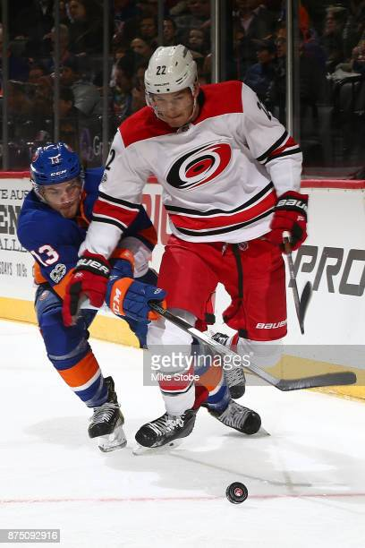 Mathew Barzal of the New York Islanders battles for the puck against Brett Pesce of the Carolina Hurricanes at Barclays Center on November 16 2017 in...