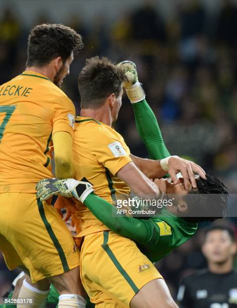 Mathew Leckie and Tomi Juric of Australia collide with Thai goalkeeper Sinthaweechai Hathairattanakool during the World Cup 2018 qualifying football...