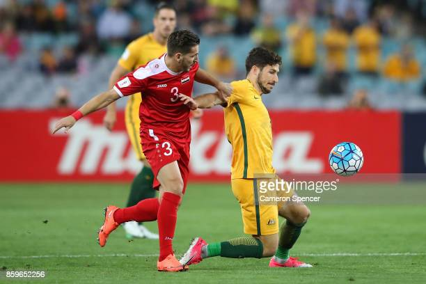 Mathew Leckie of Australia is tackled during the 2018 FIFA World Cup Asian Playoff match between the Australian Socceroos and Syria at ANZ Stadium on...