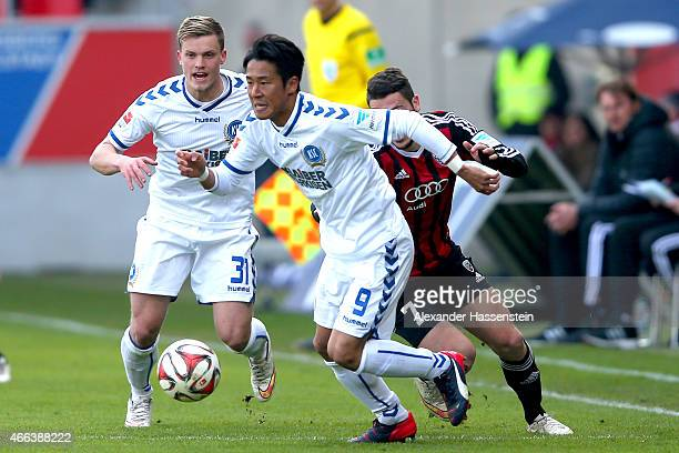 Mathew Leckie of Ingolstadt battles for the ball with Hiroki Yamada of Karlsruhe and his team mate Philipp Max during the Second Bundesliga match...