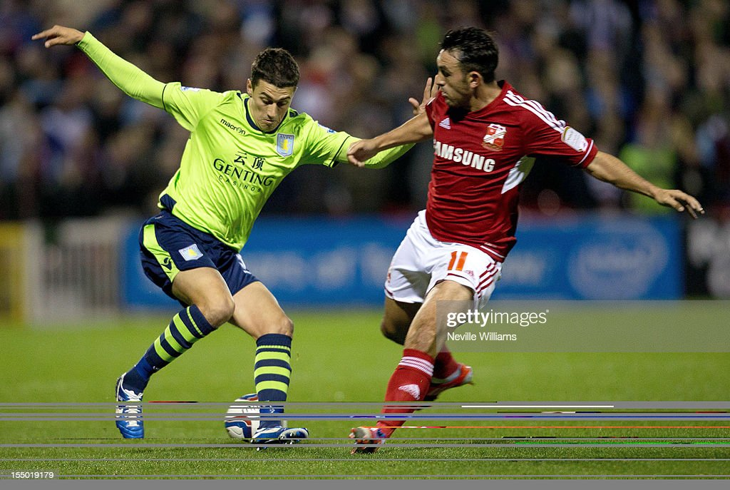 Mathew Lowton of Aston Villa is challenged by <a gi-track='captionPersonalityLinkClicked' href=/galleries/search?phrase=Gary+Roberts&family=editorial&specificpeople=202846 ng-click='$event.stopPropagation()'>Gary Roberts</a> of Swindon Town during the Capital One Cup Fourth Round match between Swindon Town and Aston Villa at the County Ground on October 30, 2012 in Swindon, England.