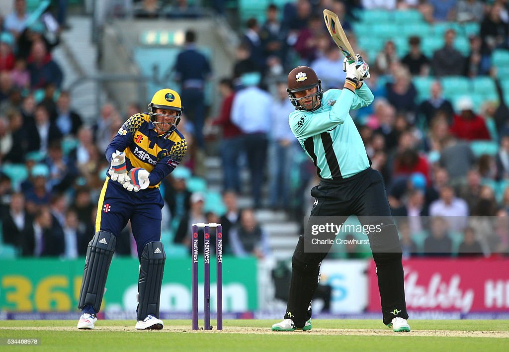 Mathew Pillans of Surrey hits out while Chris Cooke (L) of Glamorgan looks on during the Natwest T20 Blast match between Surrey and Glamorgan at The Kia Oval on May 26, 2016 in London, England.