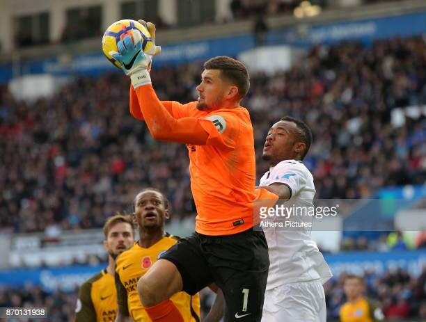 Mathew Ryan of Brighton grabs the ball while challenged by Jordan Ayew of Swansea City during the Premier League match between Swansea City and...