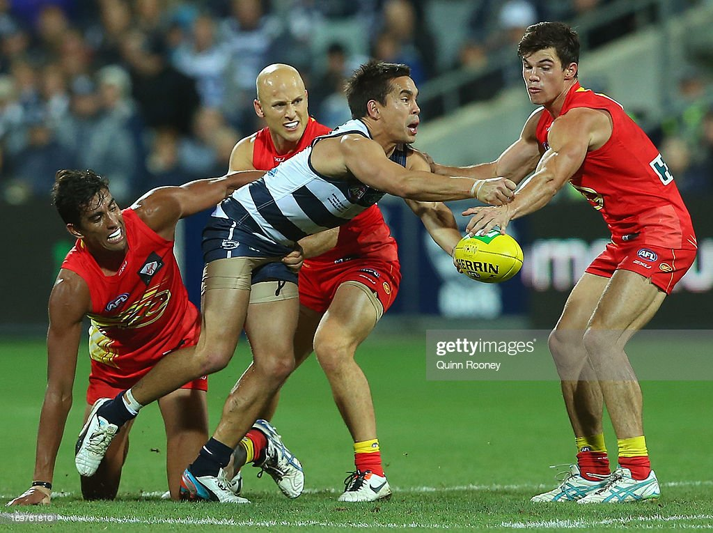 Mathew Stokes of the Cats handballs whilst being tackled by <a gi-track='captionPersonalityLinkClicked' href=/galleries/search?phrase=Gary+Ablett&family=editorial&specificpeople=206196 ng-click='$event.stopPropagation()'>Gary Ablett</a> of the Suns during the round ten AFL match between the Geelong Cats and the Gold Coast Suns at Simonds Stadium on June 1, 2013 in Geelong, Australia.