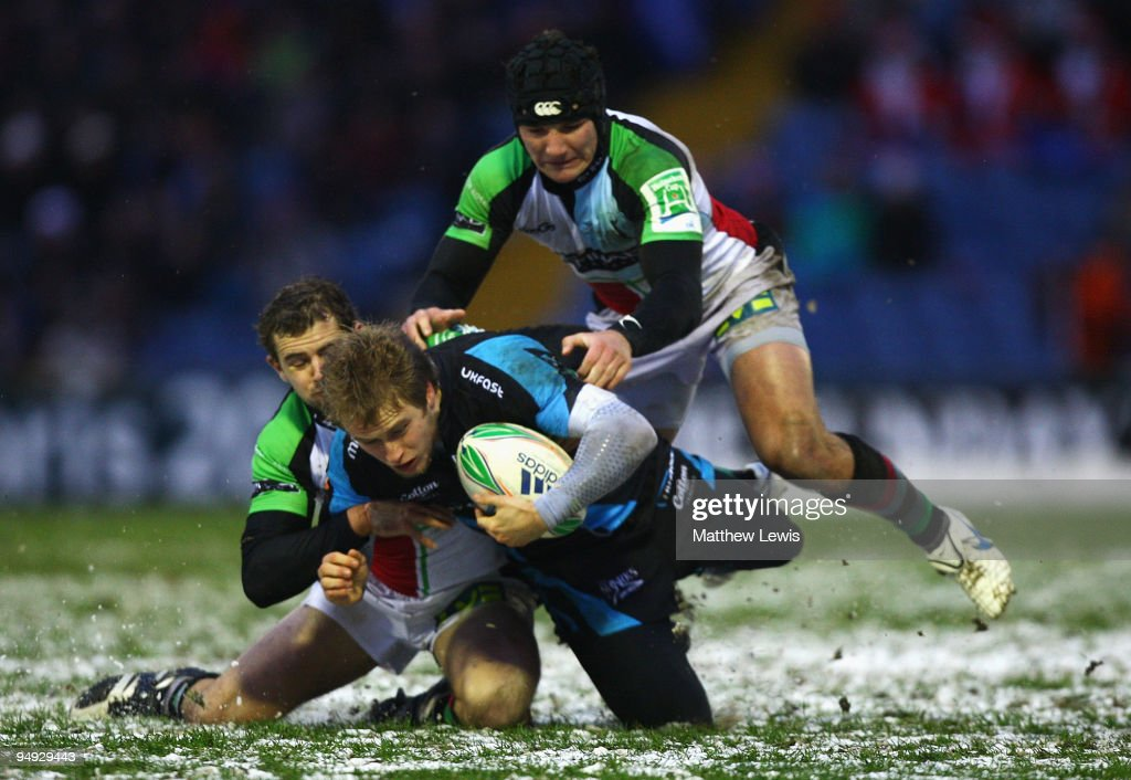Mathew Tait of Sale is tackled by Nick Evans and George Lowe of Harlequins during the Heineken Cup match between Sale Sharks and Harlequins at...