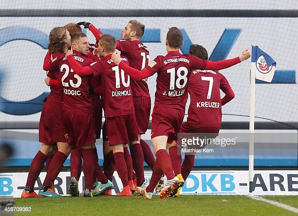 Mathias Fetsch of Dresden jubilates with team mates after scoring the third goal during the third league match between FC Hansa Rostock and SG Dynamo...