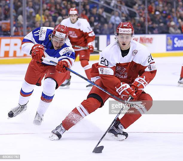 Mathias From of Team Denmark skates away from a checking German Rubtsov of Team Russia during a QuarterFinal game at the 2017 IIHF World Junior...