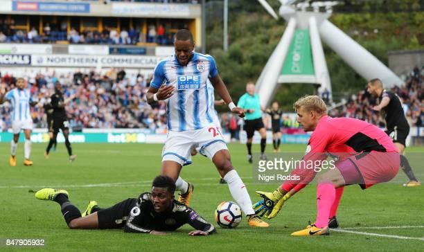 Mathias Jorgensen of Huddersfield Town and Demarai Gray of Leicester City battle for possession as Jonas Lossl of Huddersfield Town collects the ball...