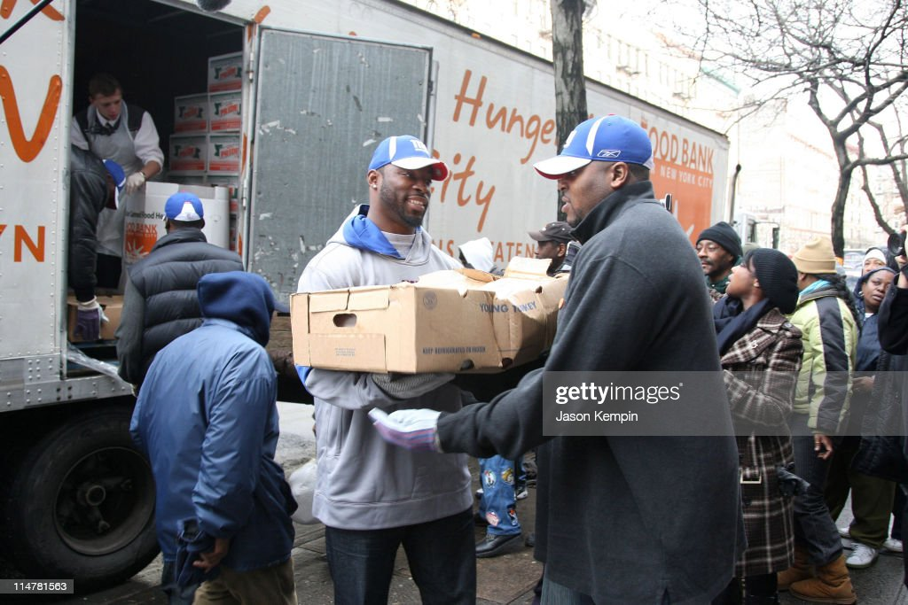 Mathias Kiwanuka Justin Tuck and Jeremy Clark of the New York Giants deliver Thanksgiving dinner to the Food Bank Community Kitchen of West Harlem...