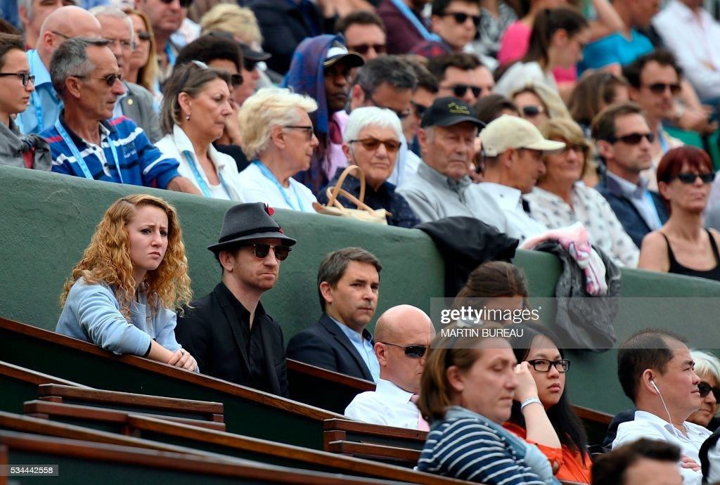 Mathias Malzieu (2nd L), lead singer of French band Dionysos, attends the men's second round match between France's Jo-Wilfried Tsonga and Cyprus' Marcos Baghdatis at the Roland Garros 2016 French Tennis Open in Paris on May 26, 2016. / AFP / Martin BUREAU