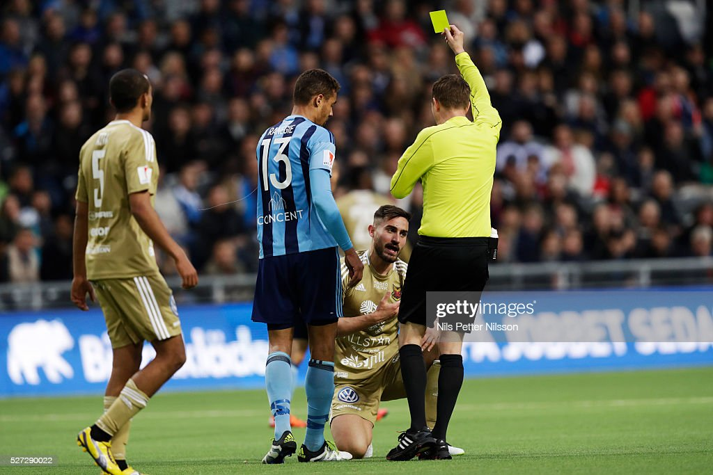 Mathias Ranegie of Djurgardens IF is shown a yellow card by Markus Strombergsson, referee, during the Allsvenskan match between Djurgardens IF and Ostersunds FK at Tele2 Arena on May 2, 2016 in Stockholm, Sweden.