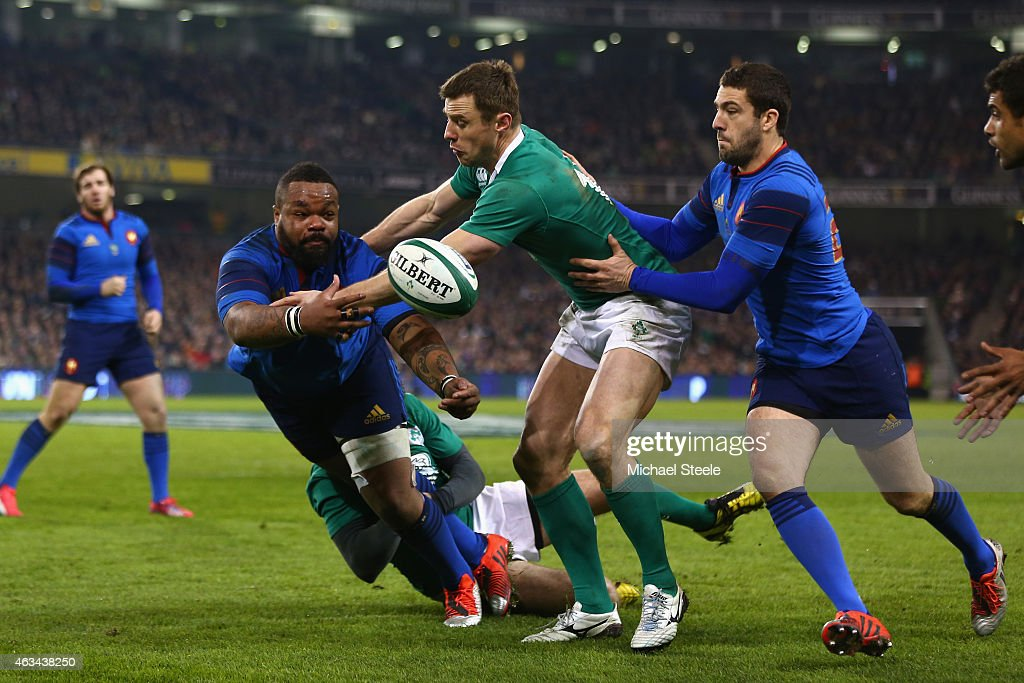 Mathieu Bastareaud of France feeds a pass as Tommy Bowe of Ireland closes in during the RBS Six Nations match between Ireland and France at the Aviva Stadium on February 14, 2015 in Dublin, Ireland.