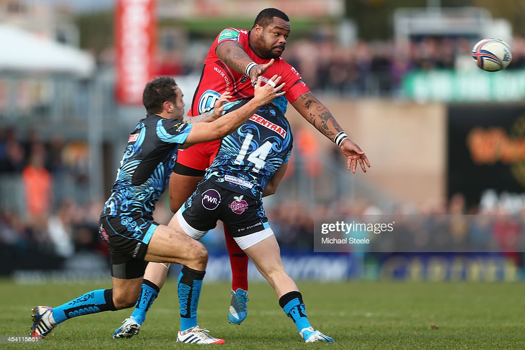 Mathieu Basteraud of offloads the ball as Jack Nowell (#14) and <a gi-track='captionPersonalityLinkClicked' href=/galleries/search?phrase=Luke+Arscott&family=editorial&specificpeople=2350778 ng-click='$event.stopPropagation()'>Luke Arscott</a> (L) of Exeter Chiefs challenge during the Heineken Cup Pool Two match between Exeter Chiefs and Toulon at Sandy Park on December 7, 2013 in Exeter, England.