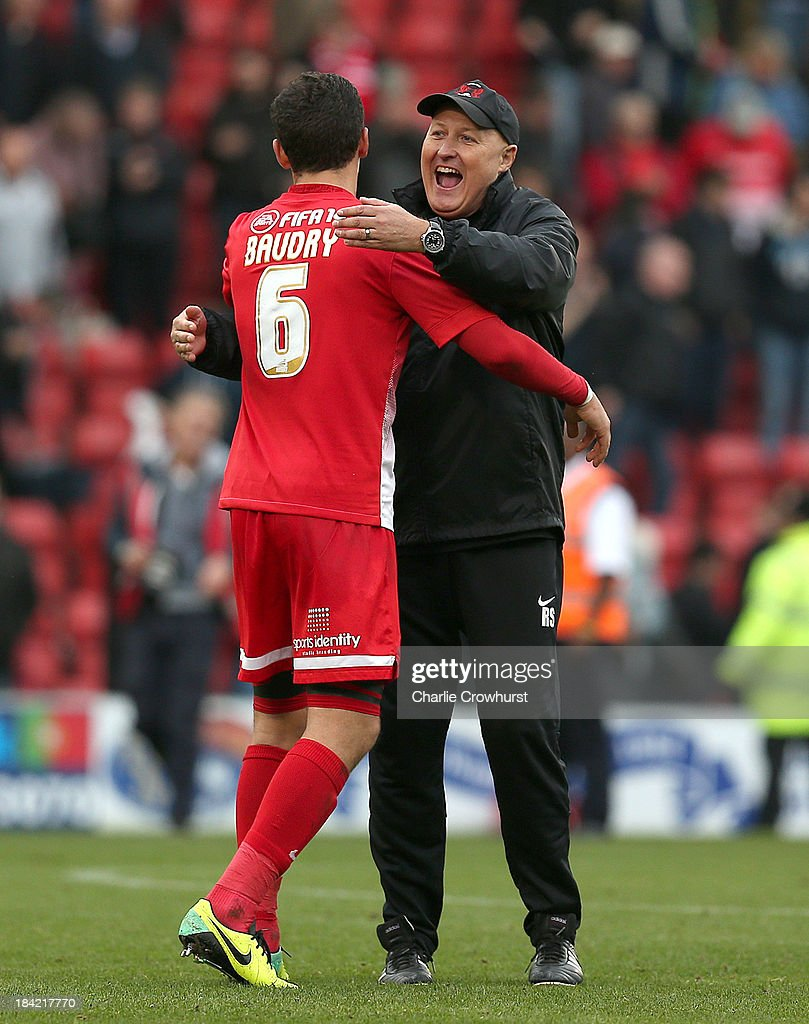 Mathieu Baudry of Leyton Orient celebrates their win with manager Russell Slade during the Sky Bet League One match between Leyton Orient and MK Dons at The Matchroom Stadium on October 12, 2013 in London, England.