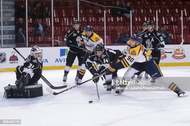 Mathieu Bellemare of the Gatineau Olympiques guards his net as Darien Kielb defends against Mathieu Samson of the Shawinigan Cataractes on October 6...