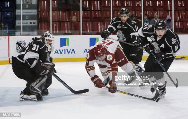 Mathieu Bellemare of the Gatineau Olympiques guards his net as Vitalii Abramov defends against Dawson Theede of the AcadieBathurst Titan who falls...
