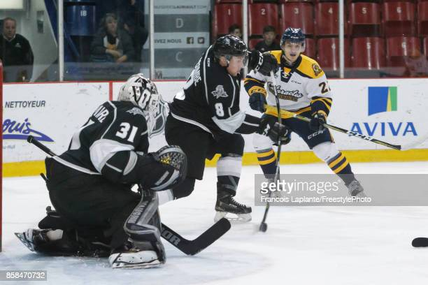 Mathieu Bellemare of the Gatineau Olympiques guars his net as PierOlivier Lacombe clears the puck against the Shawinigan Cataractes on October 6 2017...